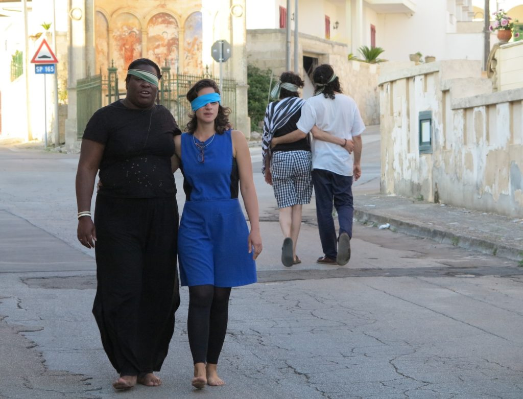 Two people walk arm-in-arm down the street partially blindfolded