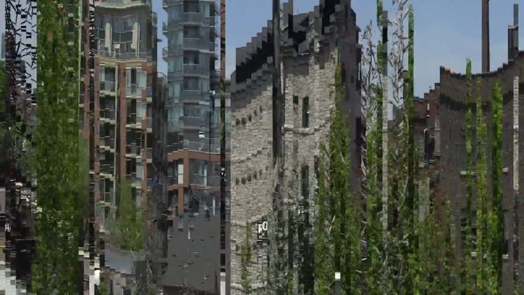 A pixelated video still of buildings and trees sliced vertically into strips of image.