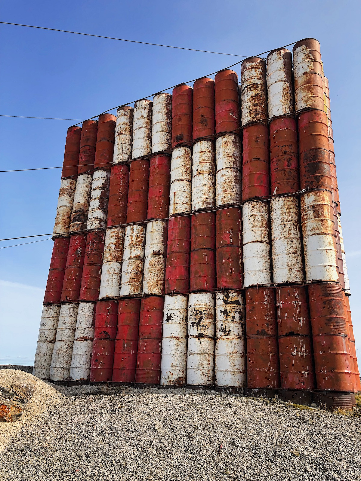 A large wall comprised of barrels arranged in a red and white checked pattern.