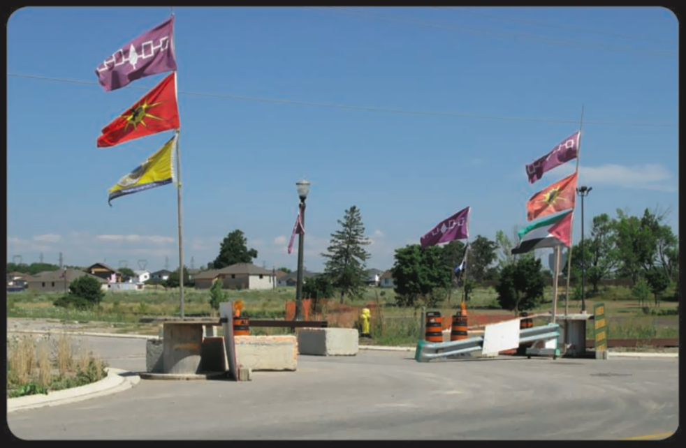 Concrete slabs, road dividers, and safety railings partially block access to a street. Flags from various Indigenous communities wave on either side of the blockade.