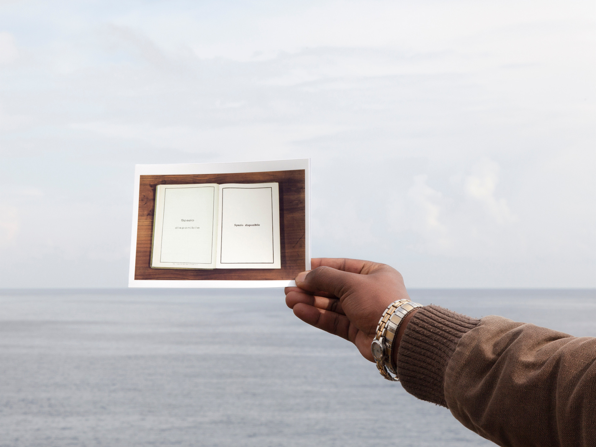 A hand with darker skin holds up a photograph of an open book against a backdrop of open water and grey skies.